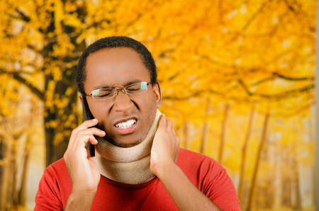 neck brace: Injured young positive black hispanic male wearing neck brace, talking on phone and hand holding support in agony, yellow abstract background. Stock Photo