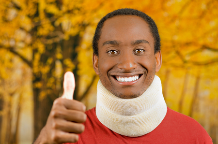 neck brace: Injured young positive black hispanic male wearing neck brace and smiling to camera giving thumb up, yellow abstract background.