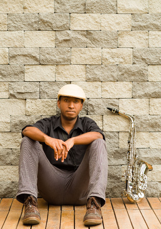 african sax: African man wearing sixpence hat and dark shirt sitting down leaning against wall, saxophone next to him.