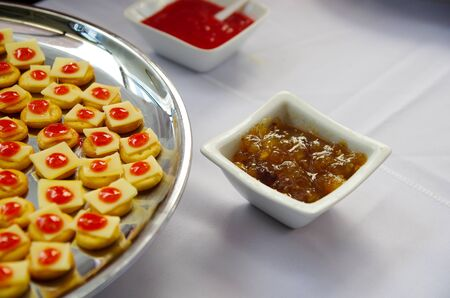 lined up: Tray of biscuits with cheee and red topping, lined up on metal plate. Stock Photo