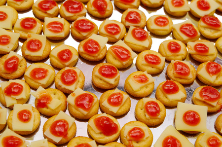 lined up: Tray of biscuits with cheee and red topping, lined up on metal surface.
