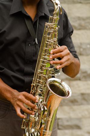 african sax: Closeup hands of man wearing dark shirt and playing saxophone.