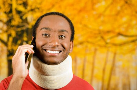 neck brace: Injured young positive black hispanic male wearing neck brace and smiling to camera, yellow abstract background.