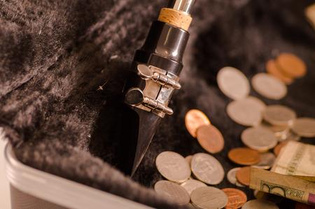 black velvet: Closeup mouthpiece saxophone lying across open instrumental casing with black velvet interior and pile of money inside.