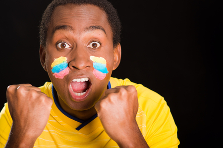 enthusiastically: Headshot dark skinned male wearing yellow football shirt in front of black background, flag facial paint, facing camera and cheering enthusiastically. Stock Photo