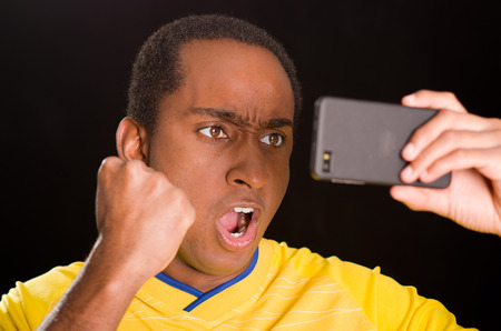 enthusiastically: Headshot dark skinned male wearing yellow football shirt in front of black background, holding up mobile phone watching screen and cheering enthusiastically.