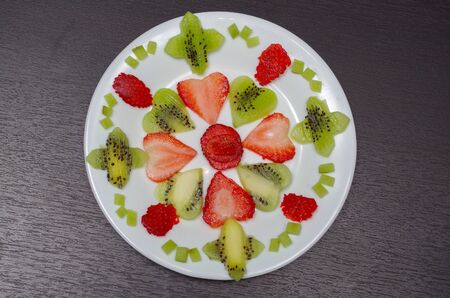 lying in: Sliced kiwi and strawberries lying in neatly placed pattern on white plate, as senn from above. Stock Photo
