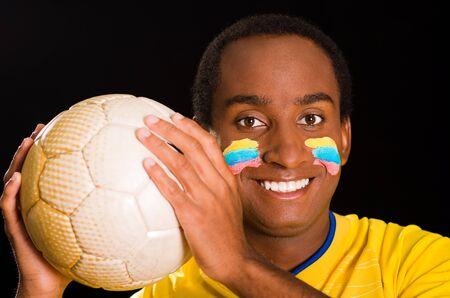 facing to camera: Headshot dark skinned male wearing yellow football shirt in front of black background, flag facial paint, facing camera holding ball and smiling.