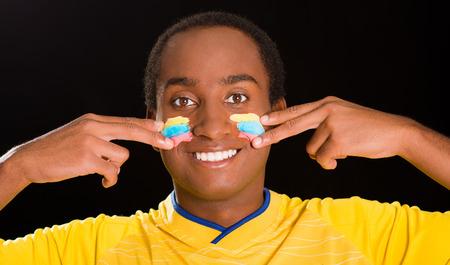 the cheeks: Headshot dark skinned male wearing yellow football shirt in front of black background, using fingers applying facepaint to cheeks.
