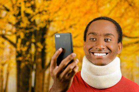 neck brace: Injured young positive black hispanic male wearing neck brace and smiling, holding up cell phone as in taking selfie, yellow abstract background.