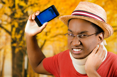 neck brace: Injured black hispanic male wearing neck brace, glasses and hat, holding cell phone making painful facial expression, yellow abstract background. Stock Photo