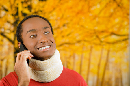 neck brace: Injured young positive black hispanic male wearing neck brace and talking on phone smiling, yellow abstract background. Stock Photo