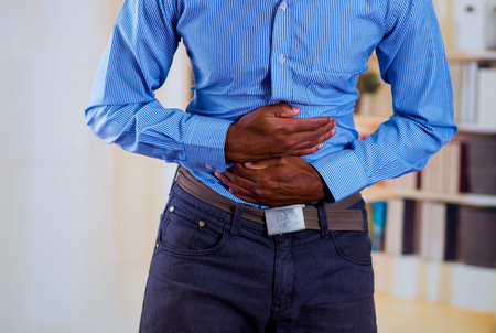 constipation symptom: Man making pressure with both hands in his stomach, strong pain. Stock Photo