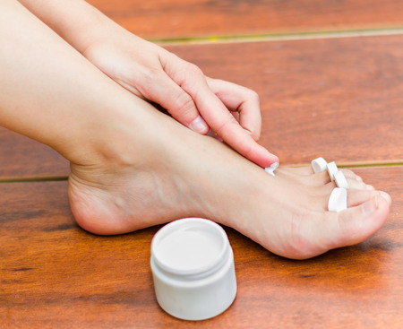 best way: A woman hand applying moisturizer in her feet, best way to hydrate the skin. Stock Photo