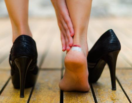Los tacones altos a veces duele, pequeña mancha blanca en el tobillo. zapatos de tacón negro en suelo de madera. Foto de archivo
