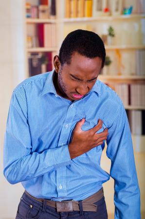 dolor de pecho: Hombre con la cara del dolor, ataque al corazón en el pecho. Mano que sostiene el pecho fuerte.