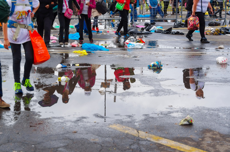 footgear: QUITO, ECUADOR - JULY 7, 2015: After raining water puddle stay on the street, people shadows on them, and walking on the sides.