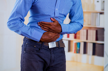 constipation symptom: Man feeling strong pain in his stomach, makes pressure with both hands.