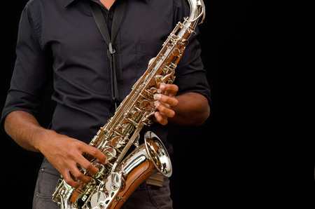 professional flute: Nice hands touching a silver saxophone, black background.