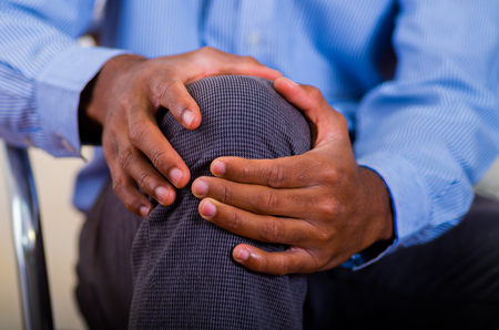 Both hands of a man making a massage on his knee, pain.