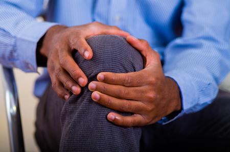 Beide handen van een man die op zijn knie massage doet, pijn. Stockfoto