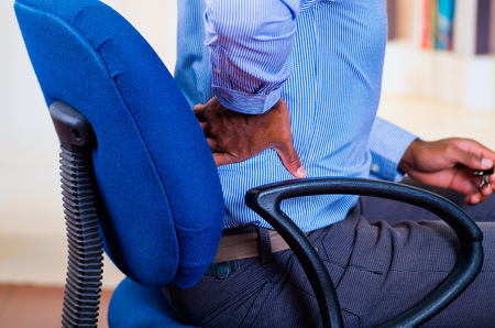 Man apparently working, sitting in a chair and holding his back, pain signal. Stockfoto