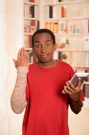 cast: Man in red shirt wearing large grey bandage over lower right arm, holding tablet in other hand and looking into camera. Stock Photo