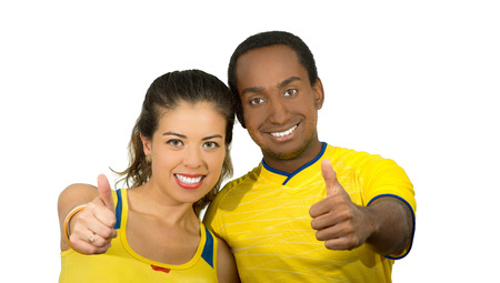 fanatics: Charming interracial couple wearing yellow football shirts giving thumbs up to camera, white studio background.