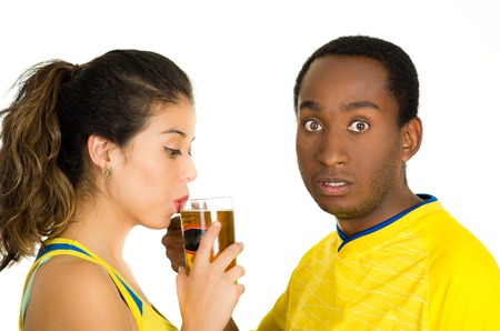 fanatics: Charming interracial couple wearing yellow football shirts, posing for camera while woman drinks from beer glass and man with surprised facial expression, white studio background.