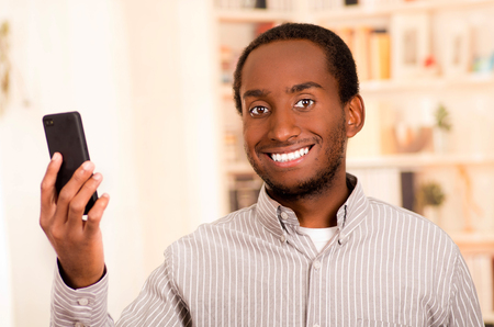 live stream listening: Handsome man wearing casual clothes holding up mobile phone looking into camera and smiling. Stock Photo