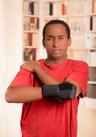 cast: Man in red shirt wearing wrist brace support on right hand posing for camera, holding his shoulder with other arm simulating painful movements.