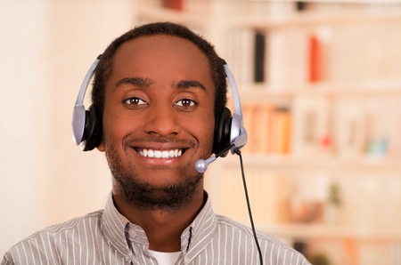 conversating: Handsome man wearing casual clothes and headset with microphone, great positive attitude smiling to camera.