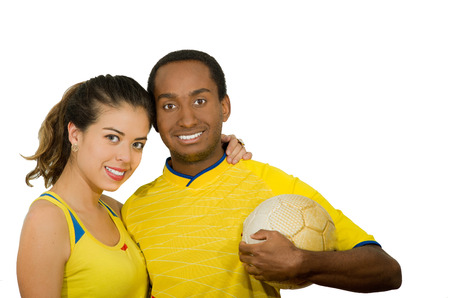 fanatics: Charming interracial couple wearing yellow football shirts, hugging friendly while posing for camera holding ball, white studio background.