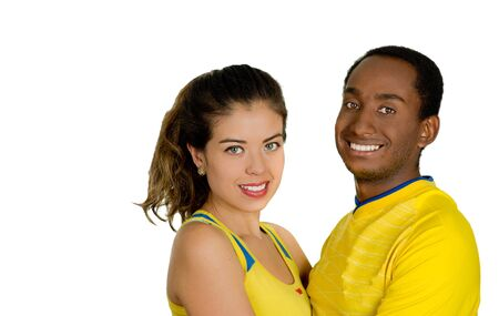 fanatics: Charming interracial couple wearing yellow football shirts, embracing friendly while posing for camera, white studio background.
