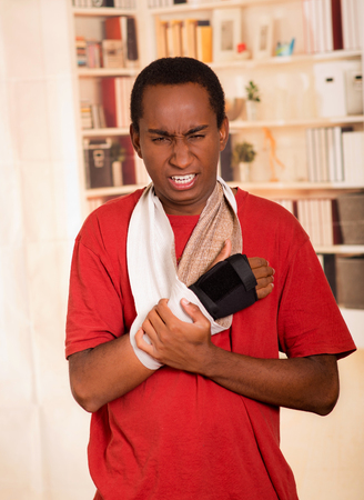 cast: Man in red shirt wearing wrist brace support on right hand posing for camera, holding his arm simulating painful movements. Stock Photo