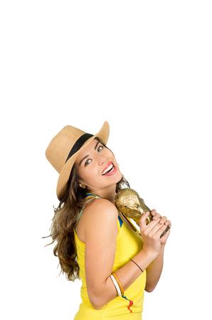 fanatics: Hispanic brunette wearing yellow football shirt and hat, posing for camera while holding trophy, white studio background. Stock Photo