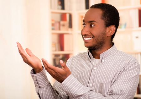 live stream listening: Man wearing casual clothes posing happily for camera, interacting using hands, bookshelves background. Stock Photo