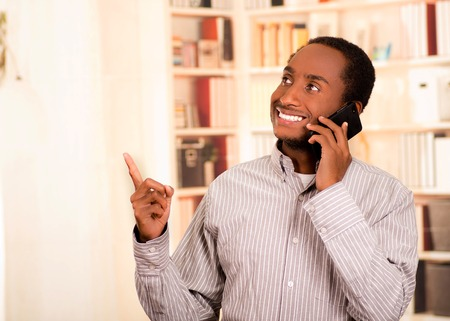 conversating: Handsome man wearing casual clothes talking on mobile phone while pointing upwards, white bookshelves background. Stock Photo