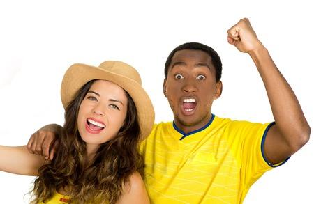 fanatics: Charming interracial couple wearing yellow football shirts cheering joyfully to camera, white studio background.