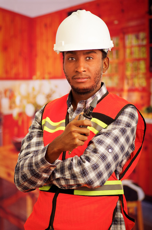 polisher: Young engineer carpenter wearing helmet, square pattern flanel shirt with red safety vest, holding small handheld electric polisher tool smiling to camera.