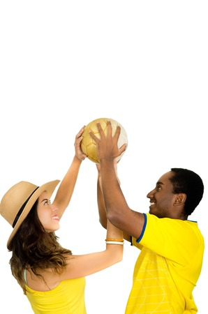 fanatics: Charming interracial couple wearing yellow football shirts holding ball up in air between each other, profile angle white studio background.