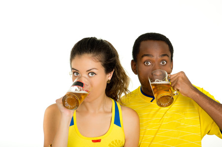 fanatics: Charming interracial couple wearing yellow football shirts, posing for camera holding beer glasses and smiling, white studio background.