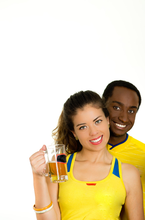 fanatics: Charming interracial couple wearing yellow football shirts, posing for camera holding beer glass and smiling, white studio background.