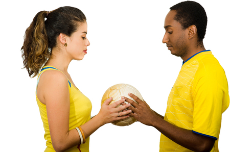 fanatics: Charming interracial couple wearing yellow football shirts holding ball between each other, profile angle white studio background.