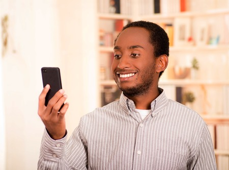 live stream listening: Handsome man wearing casual clothes holding up mobile phone looking at screen and smiling. Stock Photo