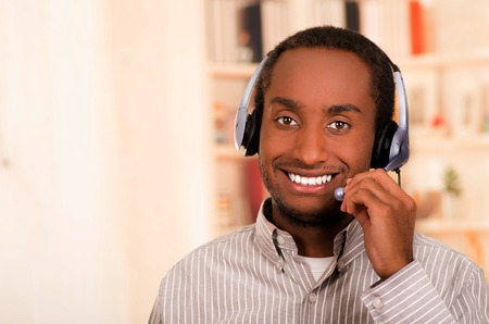 live stream listening: Handsome man wearing casual clothes and headset with microphone, great positive attitude smiling to camera.