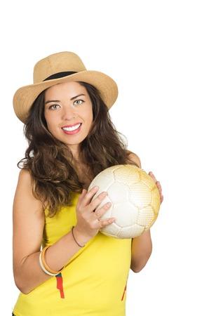fanatics: Hispanic brunette wearing yellow football shirt and hat, posing for camera while holding ball, white studio background.