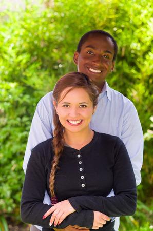 Hermosa joven pareja interracial en el entorno de jardín, abrazando y sonriendo feliz a la cámara.