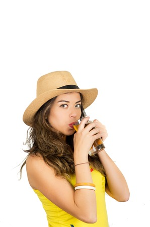 fanatics: Hispanic brunette wearing yellow football shirt and hat, posing for camera while drinking from beer glass, white studio background. Stock Photo