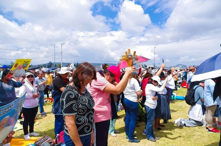 blessings: QUITO, ECUADOR - JULY 7, 2015: People praying and raising their crosses to receive blessings, pope Francisco mass.